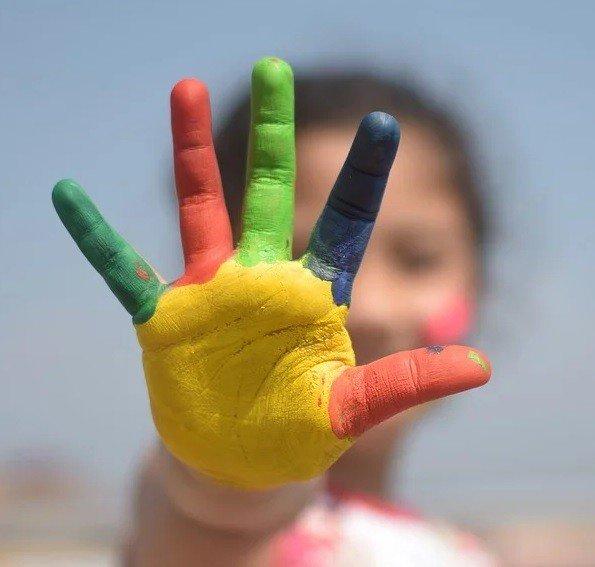 Mano extendida con la palma y los dedos pintados con colores llamativos