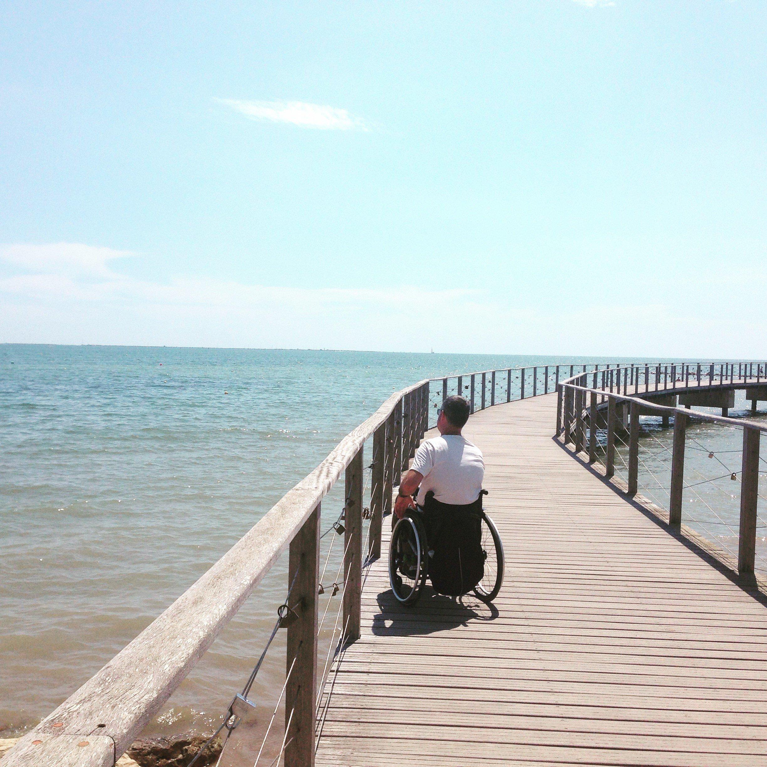 Persona usuaria de silla de ruedas en una pasarela de madera sobre el mar