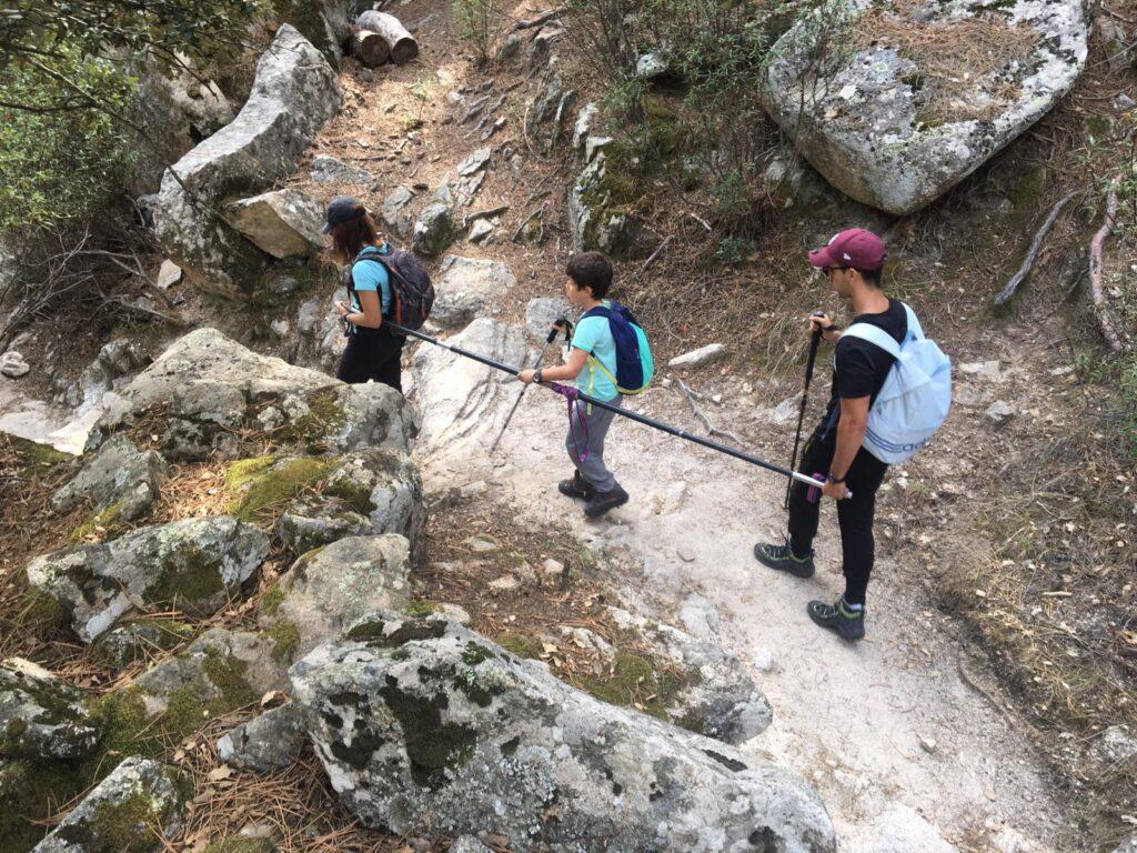 Dos adultos guían a un niño ciego por el monte  ayudados por una barra direccional