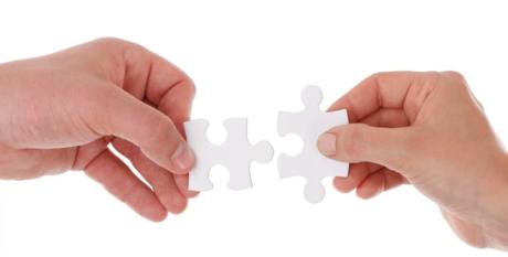 Dos manos unen dos piezas de puzzle