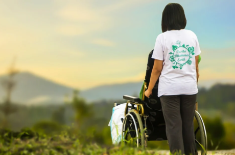 Persona de pie dirige una silla de ruedas  mientras contemplan un aterdecer