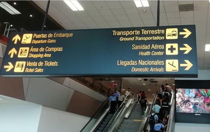 Letrero de un aeropuerto con varios pictogramas que indican: Puertas de embarque, área de compras, venta de tickets, transporte terrestre, sanidad aérea, llegadas.