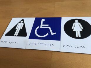 Cartelería con pictograma masculino, persona con discapacidad y femenino. Contraste cromático y braille