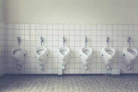 Aseo masculino con 6 urinarios  colocados frente a una pared