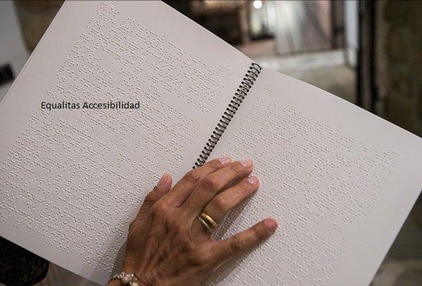 Carta menú en braille. Una mano tocando le texto en braille