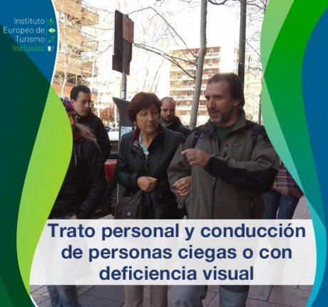Grupo de personas paseando. En primer plano un hombre de mediana edad guía a una mujer ciega por las calles de una ciudad.