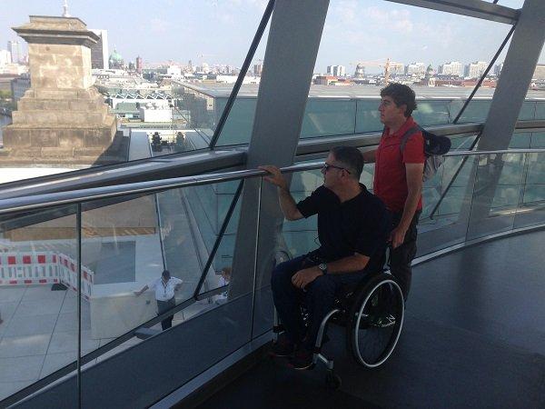 Dos personas en el interior del Reichstag escuchando las explicaciones de la audioguía